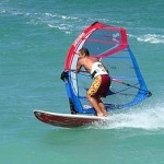 A windsurfer with modern gear tilts the rig an...